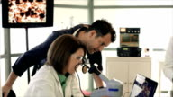 CSI Team Looking at Evidence on Microscope video