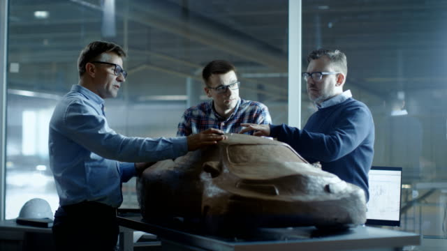 Team of Automotive Design Engineers Discusses New Prototype Model Made of Plasticine Clay. They Work in a Large Car Factory. video