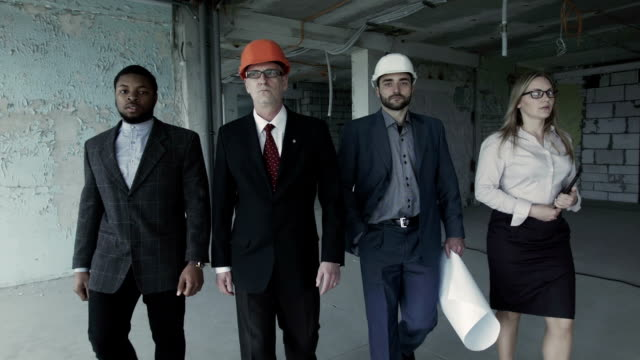Team of builders in suits, hard hat, move, look directly into camera. Black man, aged engineer video