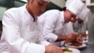 Team of chefs garnishing spaghetti dishes with basil leaf video
