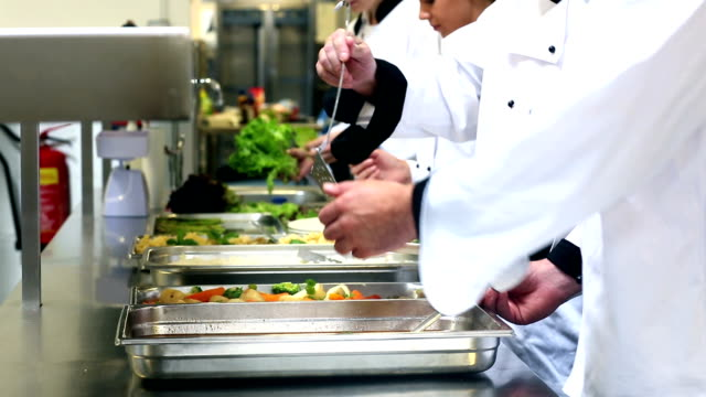 Team of chefs working at the order station video