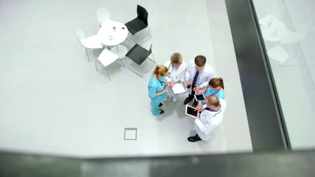 Team of doctors interacting with each other in corridor video