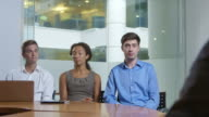 Team of employees face the boss for a business chat. video