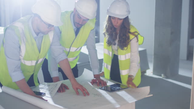 Team of Engineers are Bending over Large Blueprint and Having Conversation, inside Building Under Construction. video