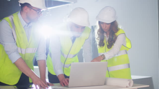 Team of Engineers in Hard Hats Having Conversation, using Laptop Computer, inside Building Under Construction. video