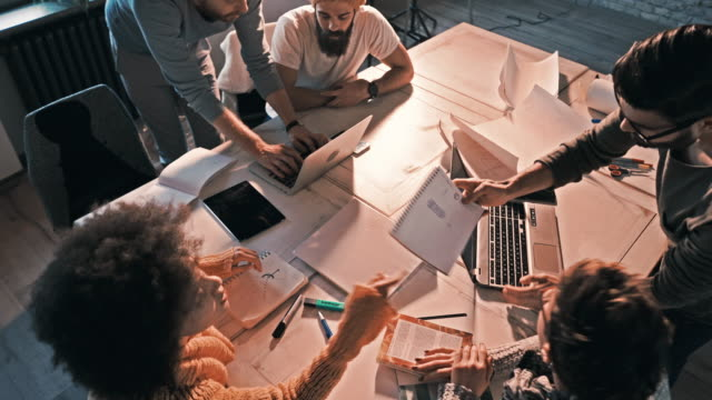 Team of freelance workers cooperating while working on a project in the office. video