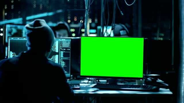 Team of Internationally Wanted Teenage Hackers with Green Screen Mock-up Display Infect Servers and Infrastructure with Malware. Their Hideout is Dark, Neon Lit and Has Multiple Displays. video