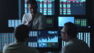 Team of stockbrokers are having a conversation in a dark office with display screens. video