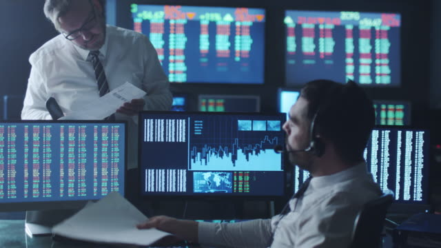 Team of stockbrokers are having a discussion in a dark office with display screens. video