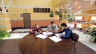 Team of students develop project at round table, discuss idea, solve problem video