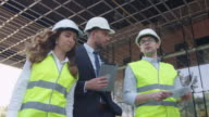 Team of Two Engineers and Businessman in Hard Hat Walking, Talking, and Using Tablet Computer. Glass Building or Skyscraper under Construction on Background. video