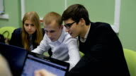 Team of young specialists in the sphere of information technology preparing to present new IT-startup to the audience. Two young male and one female students are working together video
