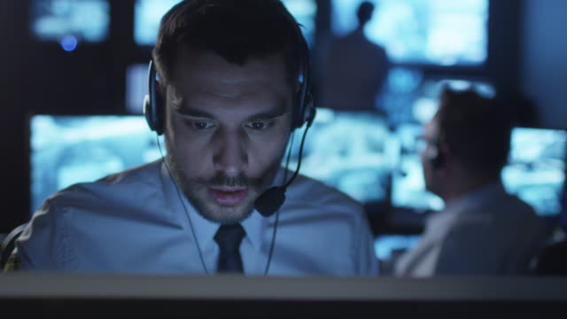 Technical support specialist is talking on a headset while working on a computer in a dark monitoring room filled with display screens. video