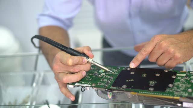 IT technician fixing a motherboard video