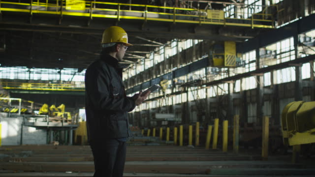 Technician in Hard Hat in Industrial Environment. Holding Tablet in Hands. video