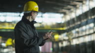 Technician in Hard Hat in using Phone in Industrial Environment. video