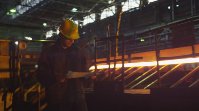 Technician in hard Hat walking Through Foundry. Industrial Environment. video