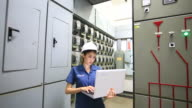 Technician inspects industrial control room. video