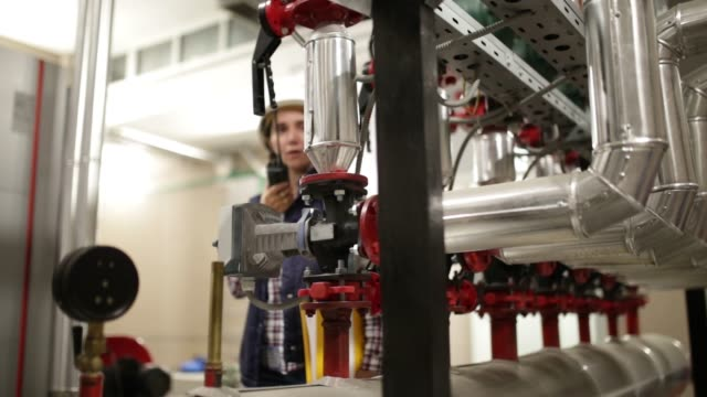 Technician working on valve in factory or utility video