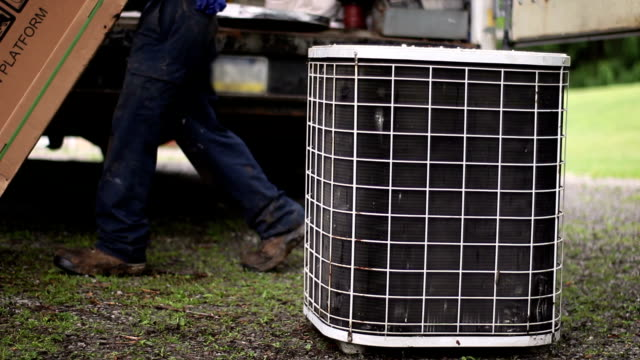 HVAC technicians wheel in a new air conditioner while old one sits unused in driveway video