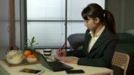 Technology and Asian people working at home with pc, beautiful Japanese young business woman at work with laptop computer and newspaper, having breakfast in living room, busy girl typing on keyboard video