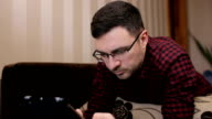 Technology, vision and people concept - man with tablet pc tired from eyeglasses at home video