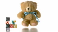 Teddy bear falling besides baby blocks and blue soother video