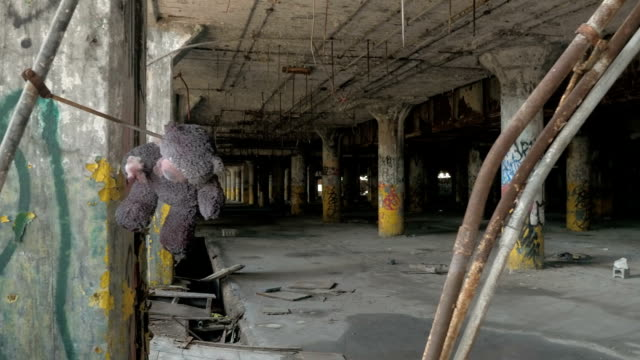 CLOSE UP: Teddy bear hanging from the hook in abandoned decaying industrial hall video