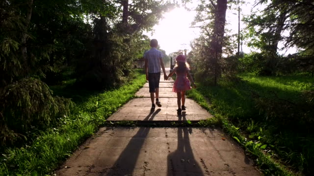 Teen boy and girl child are on track in the park. Brother and sister holding each other's hands. video