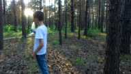 Teen boy drinks water from a bottle. Summer evening in the forest at sunset. video