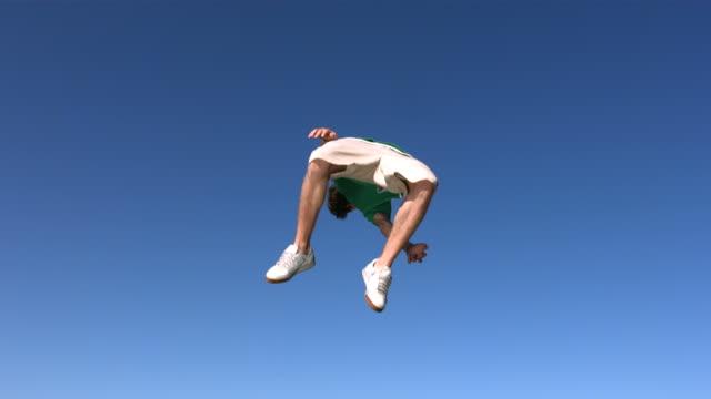 Teen boy flips in sky, slow motion video