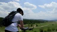 Teen boy on bike using digital tablet video
