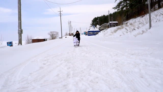 Teen boy sledding girl child. Girl is very happy that her brother sledding. Children are passionate about winter fun. A cloudy winter day. Slow motion. video