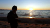 Teen boy standing at the water's edge on the shores of a large lake. video