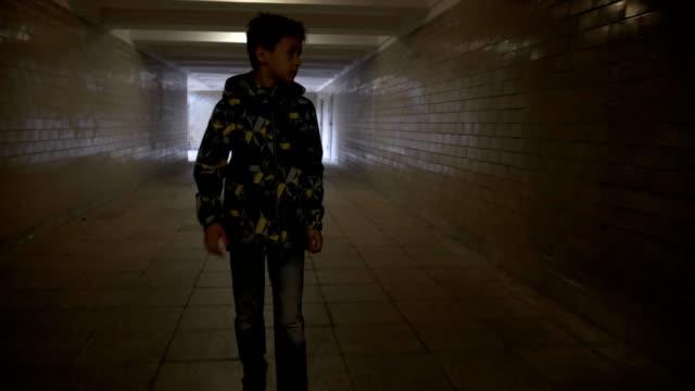 Teen boy walking alone in a narrow tunnel in the city video