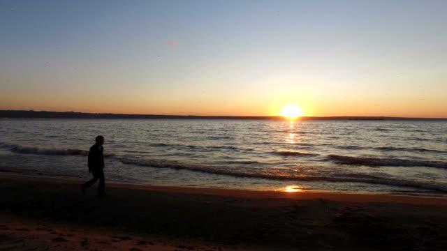 Teen boy walking along the shore of a large lake. It runs along the water's edge. video