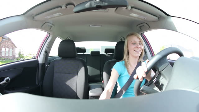 Teen driving car, wide angle view video