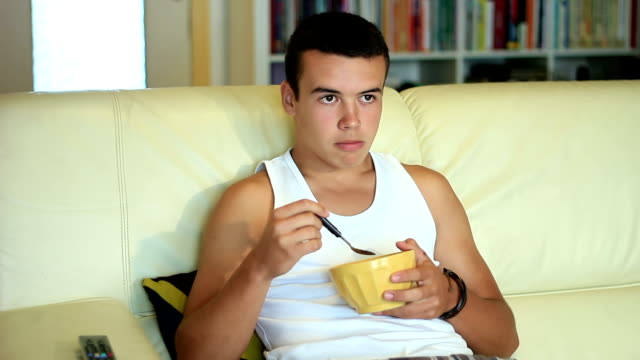 Teen eating cornflakes  while watching television video