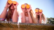 Teen girl friends holding up oranges for eyes video