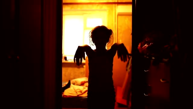 teen girl in a zombie is orange silhouette stretched hands video