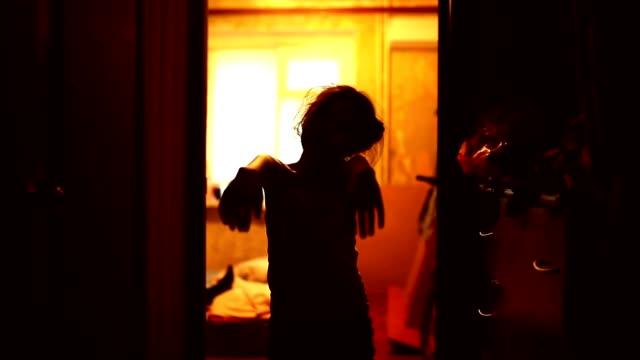 teen girl in zombie is orange silhouette stretched indoor hands video