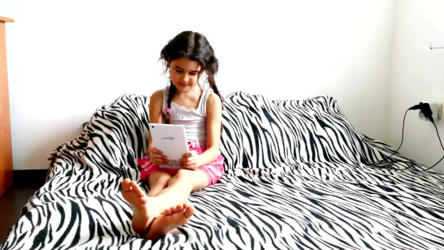 teen girl playing tablet sitting on bed video