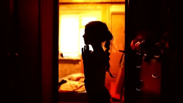 teen girl praying silhouette in a corridor brown evening religion video