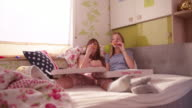 Teen girls in a bedroom smiling at a giant pizza video