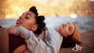 Teen grunge girls lying on a harbor wall together video