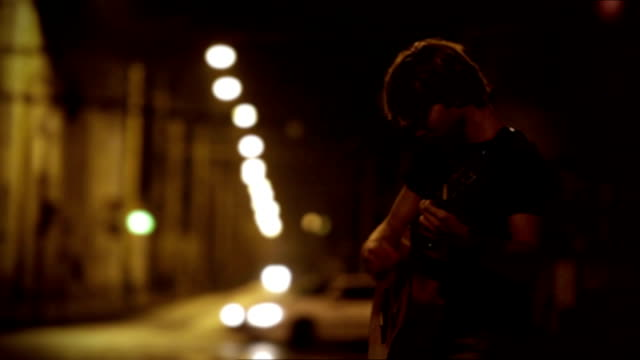 Teen guitarist playing on the night street while cars pass him by video