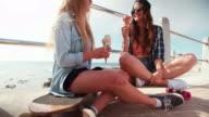 Teen hipster friends enjoying ice cream at the beachfront video