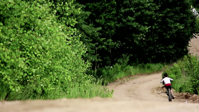 Teen rides a bicycle on a country road long video