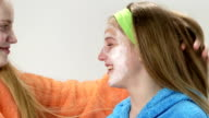 Teen skin care treatment face of teenage girl with applied facial cream mask video