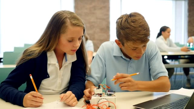 Teenage boy and girl work together on robotics project in technology class video